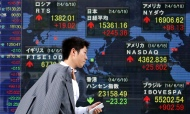 A pedestrian holding his mobile phone walks past an electronic board showing the stock market indices of various countries outside a brokerage in Tokyo June 19, 2014. Japan's Nikkei share average jumped 1.6 percent to a 4-1/2-month high on Thursday after the Federal Reserve expressed confidence on the U.S. economy and committed to its dovish monetary policy, which spurred buying from foreign investors. REUTERS/Yuya Shino (JAPAN - Tags: BUSINESS) - RTR3UKUG