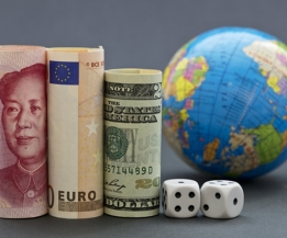 Yuan, euro, and collar next to black and white dice with globe in background. When risks are worldwide, business and investment decision makers take into account larger, international strategies.